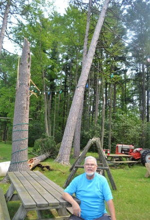 Pastor Richard King of Fairhaven Baptist Church at the south edge of Oconto sits at a picnic table in front of one of 13 trees behind the church that was snapped off in high winds early Tuesday morning, July 27.
