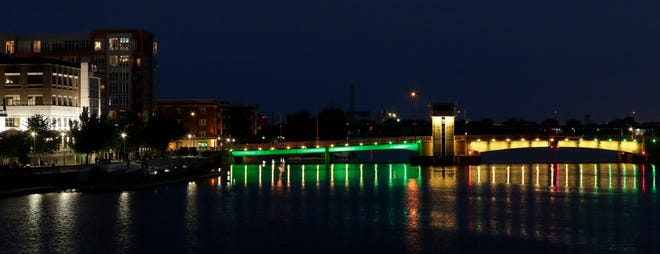 Green Bay's Walnut Street bridge, which was officially named the Bart Starr Memorial Bridge by Gov. Tony Evers on July 27, 2021, is lit up with green and yellow lights to celebrate the announcement.