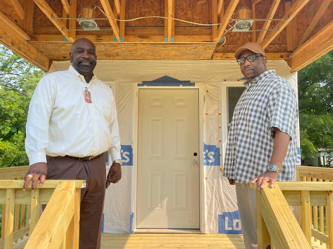 Bishop Gregory Draper and Bishop Cory Rogers stand on the front porch of one of the transitional homes on Patten Street they had built for their Hands of Hope for Housing project in Marion.