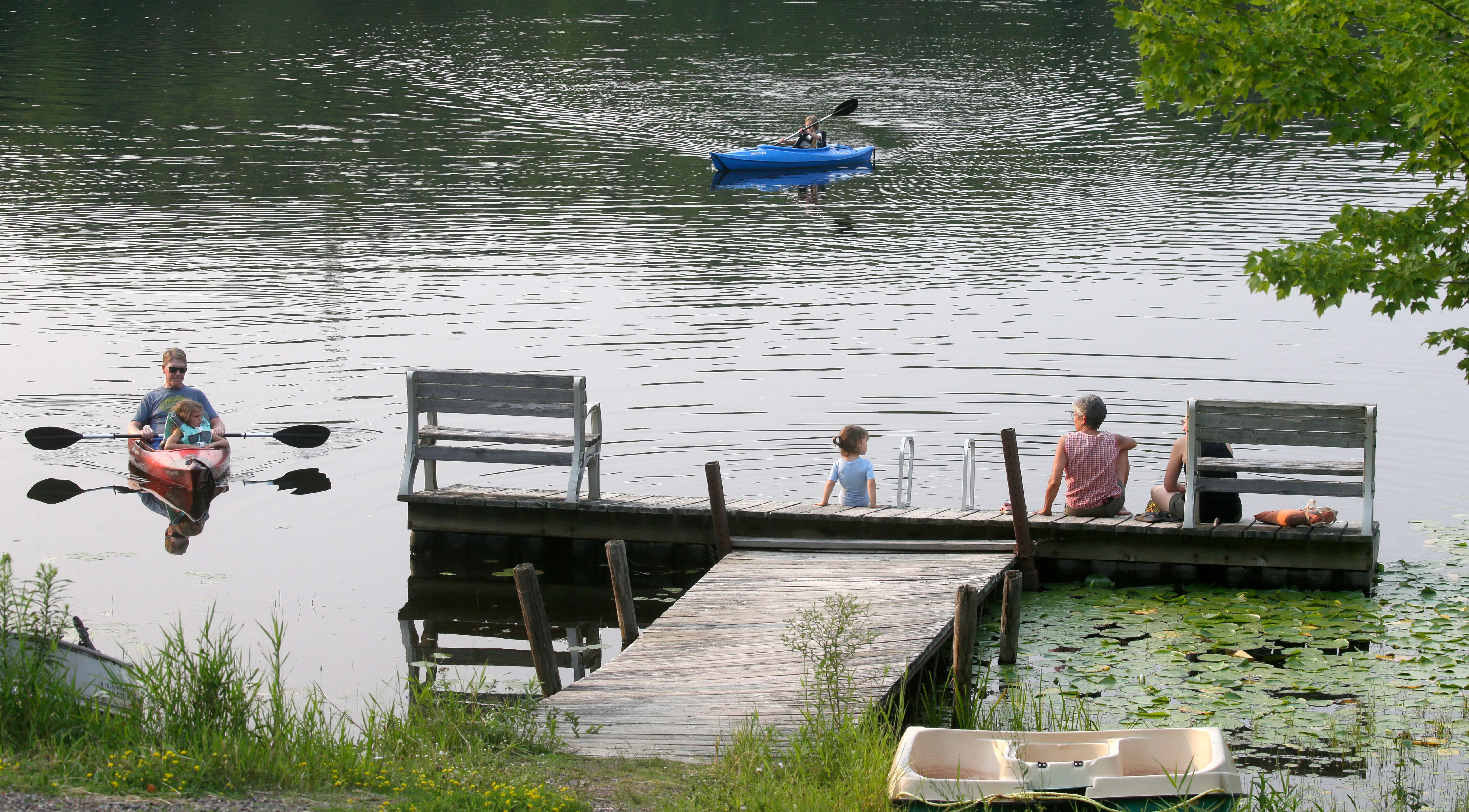 """Guests at High Point Village enjoy Bass Lake Tuesday, July 27, 2021, in rural Price County near Ogema, Wis. Kathleen Blomberg, the owner of the small resort, says, about the internet, """"It's always slow. I'm used to it, but people from away are not."""""""
