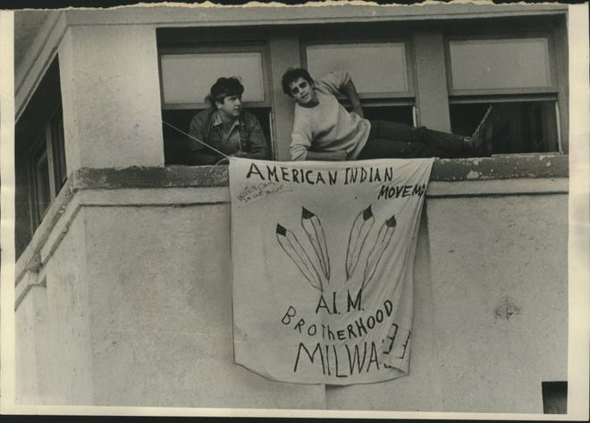 Two members of a Native American group that took over the abandoned Coast Guard Station near McKinley Beach in 1971 fly their flag from the top windows of the building.
