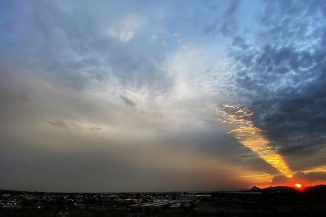 The setting sun beams light towards a dust storm covering parts of metropolitan Phoenix, July 27, 2021.