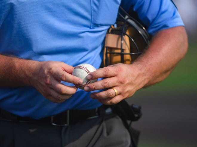 An umpire looks over one of the baseballs used in the American Legion state baseball championship on Tuesday, July 27, 2021 at Aspen Park in Brandon.