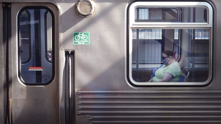 A commuter wears a face mask as she rides an L train through the Loop on July 27, 2021 in Chicago, Illinois. The Centers for Disease Control and Prevention (CDC) is expected to recommend that fully vaccinated people begin wearing masks indoors again in places with high Covid-19 transmission rates as the delta variant begins to cause a spike in coronavirus cases in some regions of the country.