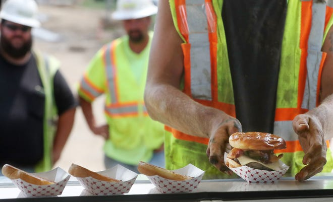 A road worker picks up his burger at the Menches Brothers food truck Wednesday in Green. John Menches, CEO of the family business, wanted to show his appreciation to the workers on the $13 million Massillon Road North project in Green by providing them a free lunch.