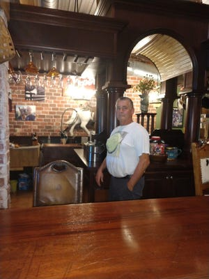 John Burkhart poses behind the bar that surrounds the kitchen he and wife Vicky built in their Hanover Township home. Burkhart, who retired as Loudonville street commissioner last month, purchased the bar in Mansfield, disassembled it and moved to his home, and rebuilt it.