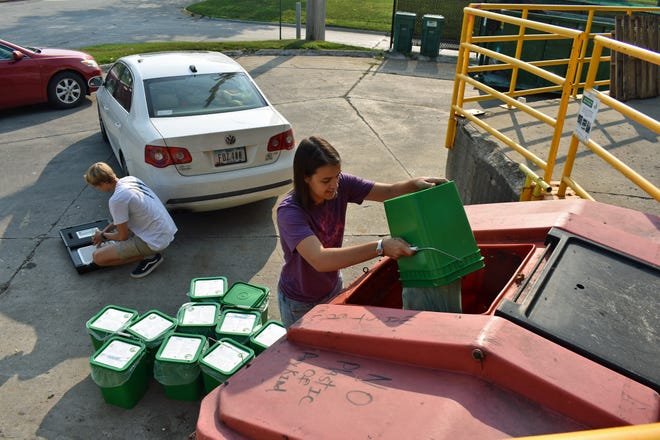 Carissa Moyna dumps the contents of a customer's food waste container into the receptacle at Ames' Resource Recovery Plant as Andrew Frank puts away the scale they used to weight the buckets.