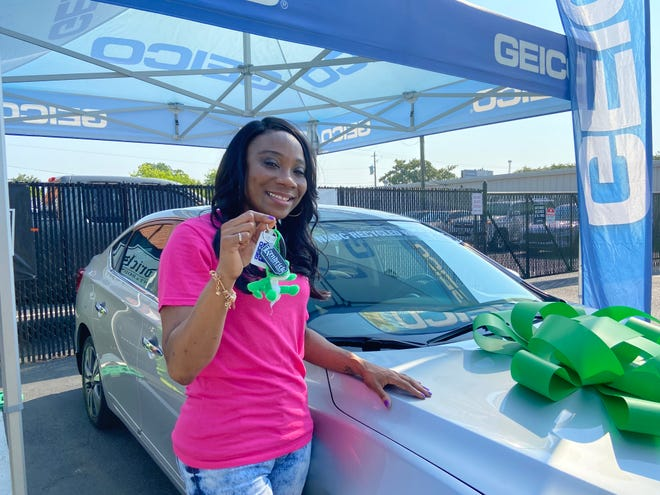 A military veteran holds up the keys to her new 2019 Nissan Sentra Thursday morning at Kendrick Paint and Body. The body shop partnered with Forces United, the National Auto Body Council and Geico to provide the vehicle to the Air Force veteran and domestic violence survivor.
