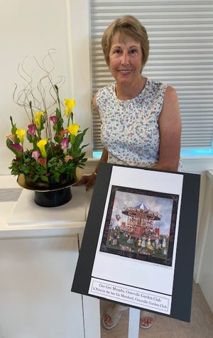 """Osterville Garden Club President Gee Gee Murphy displays her """"Art Blooms at Heritage"""" arrangement inspired by the colorful work of the late Elizabeth Mumford."""