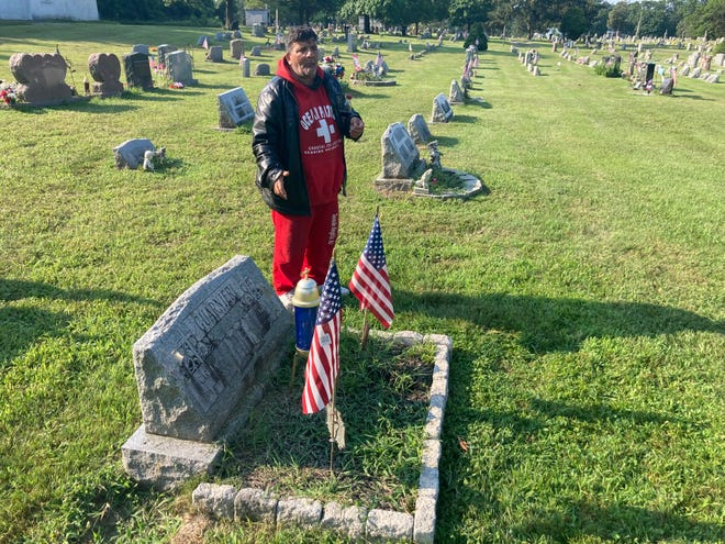 """Charles Guanieri, 61, at his grandparents' grave at the Beverly Monument Cemetery in Edgewater Park. He was made to remove an elaborate display that included statues, a snowman and life preservers. """"Yeah, life preservers,"""" he said. """"Two of 'em. The kind you throw to somebody if they're drowning."""""""
