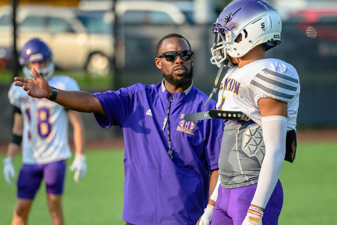 Hickman head coach Cedric Alvis talks to senior defensive back Jaiden Tandy during practice in late July.