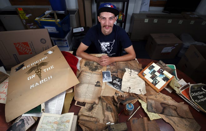 Custodian Christian Lemaster displays some of the items found during the renovations to the 1923 section of Grandview Heights High School.