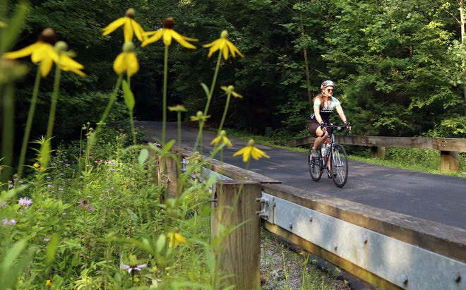 Alison Miller of Delaware rides through Hogback Ridge Park during the 18th annual Delaware County Friends of the Trail Community Ties Bicycle Tour on July 24. Bikers had the option of riding 31, 62 or 100 miles as well as an 8-mile family ride. Proceeds from the event support the section of the Ohio to Erie Trail in Delaware County.