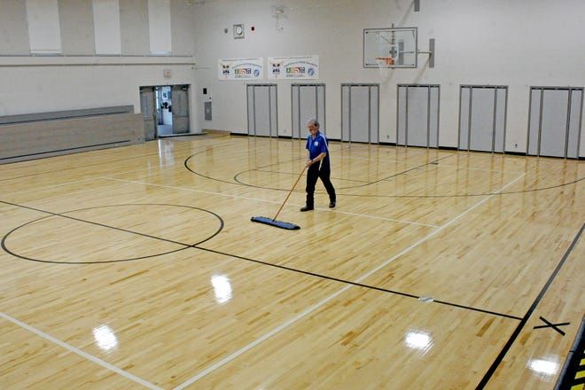 St. Mary School custodian Emerson Hageman gives the school's new gym floor a clean sweep. The floor, which was installed by Ohio Floors, replaced the original concrete floor from when the school was built in 1963.