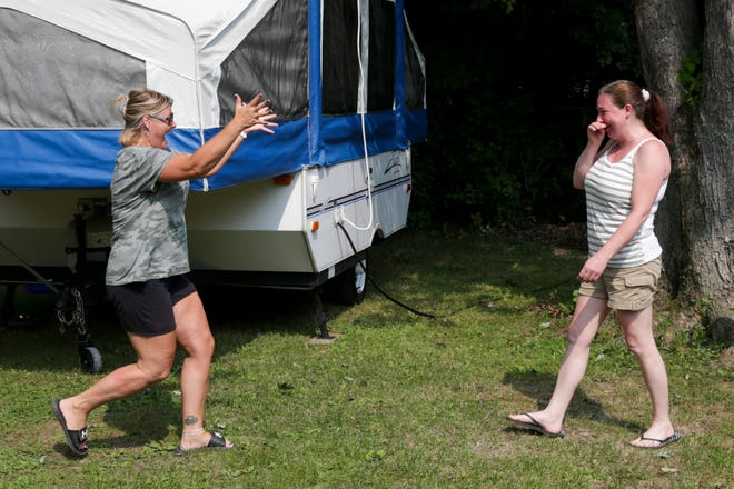 Long-time friends Tara McCarthy of Lowell, Ind., left, and Angie Merkle of Adrian react as they meet each other for the first time in person Friday, July 23, 2021, at the Indiana Beach Campgrounds in Monticello, Ind.