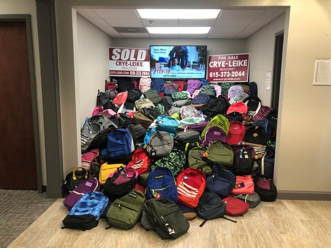 Hundreds of backpacks collected by Middle Tennessee's  Crye-Leike Real Estate Services are stacked high, ready to be donated to Youth Villages.