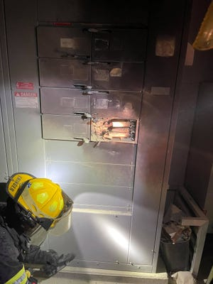 Firefighters examine a circuit breaker box after an electrical fire at the Target in West Burlington on Thursday, July 29.