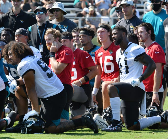 Jaguars players, including Trevor Lawrence (16), listen to head coach Urban Meyer during Thursday's training camp session.