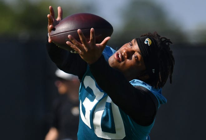 Jaguars RB (30) James Robinson stretches for the ball as he warms up with teammates at the start of the Jacksonville Jaguars training camp session at the practice fields outside TIAA Bank Field in Jacksonville, FL Thursday, July 29, 2021.  [Bob Self/Florida Times-Union]