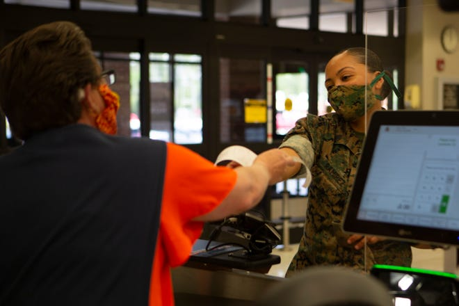 A Marine wears a face covering while grabbing a receipt from a cashier at the commissary on Marine Corps Air Station New River, April 10, 2020.