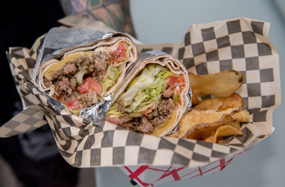 A freshly-prepared bodega chopped cheese wrap with potato chips is headed to a hungry customer from Stephen LeMasters' Grill 'Em All food stand at the Keller Station Farmers Market.