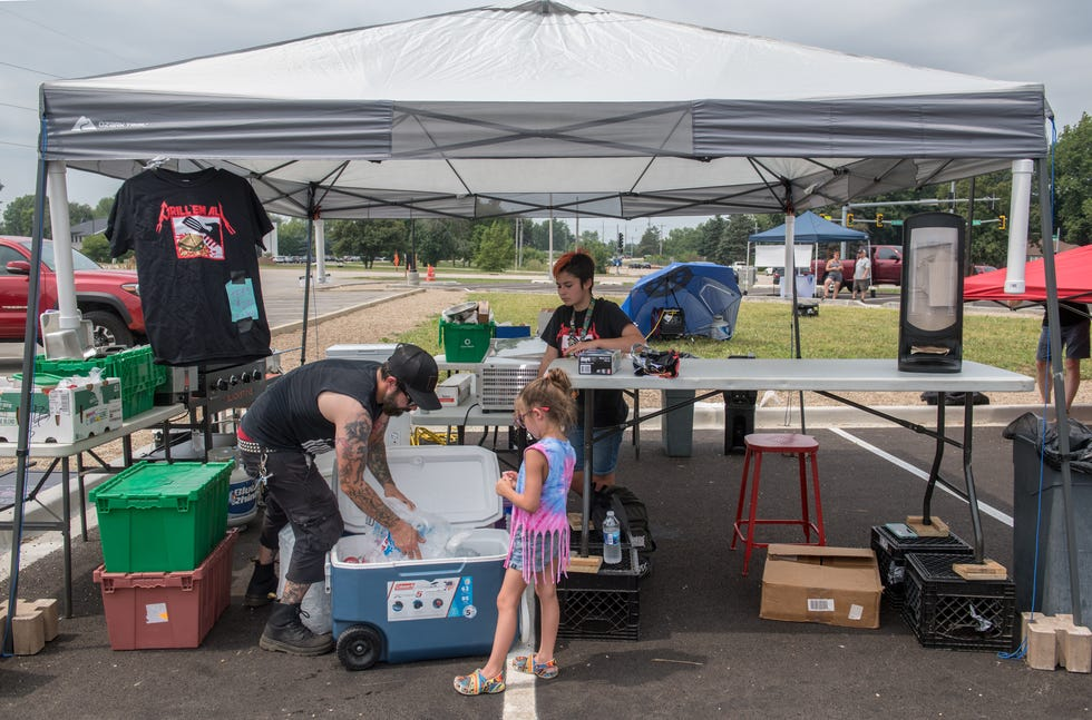 Stephen LeMasters. left, and his daughters Marley, 12, in background, and Remie, 8, assemble the many parts of their pop-up food stand Grill 'Em All at the weekly Keller Station Farmers Market in Peoria.