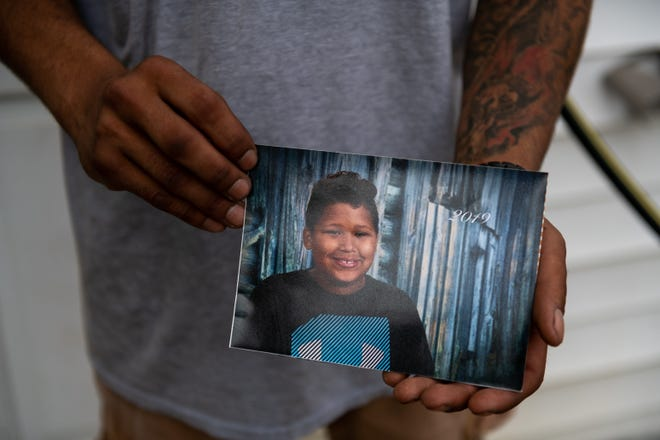 Jerome Ware, Deshawnteris Edwards' godfather, holds a photo of Deshawnteris at his home in East Peoria on Wednesday, July 28, 2021. Ware said that parents need to lock up their guns and keep them away from kids.