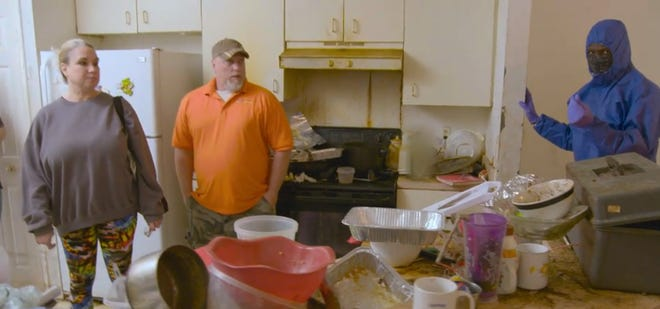 """Missy and Mike Dalton of Lakeland stand in a messy home in this screenshot taken from the A&E series """"Dirty Rotten Cleaners."""" (A&E)"""