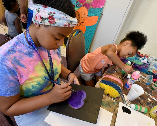 Coryssa McCray, 11, works on her purple heart painting while Madilynn Overstreet, 5, touches up her cement leaf relief sculpture piece for the new sharing garden at the Opportunity Center at the Arthur Lesow Community Center. The children created their works of art as part of a summer camp offered at the center.
