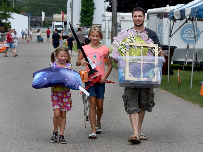 Jade Blevins-Henning, 9, (center) with the help of her dad George Henning and sister Jasmine, 5, bring fourteen 4-H projects to enter at the Monroe County Fair Thursday.  A member of the Raisinville Wranglers, Blevins-Henning brought wreaths, rockets, chimes, pillow and more.