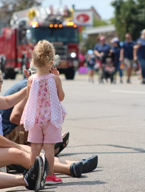 A young girl watches the Monroe County Fair Parade with her family in 2019. Officials expect a smaller than average parade this year