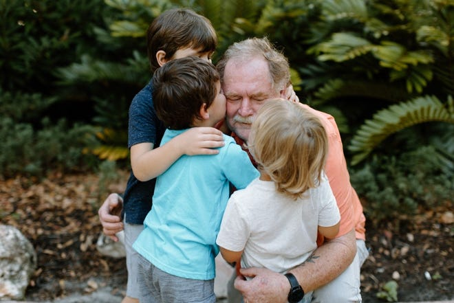Michael Wright, former chief of the Niceville and East Niceville fire departments, hugs his three grandchildren. Wright is battling Stage 4 cancer, and his family and friends have started a GoFundMe account to help fund the cost of surgery and treatment.
