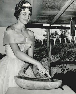 Rush Springs Watermelon Festival queen Jeri Jones slices a ripe watermelon in 1961.