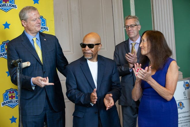 Darrell Washington, center, is named as the state's first VaxMillions winner Thursday at an announcement with Gov. Charlie Baker, Lottery Director Michael Sweeney, rear, and Treasurer Deborah Goldberg at right.