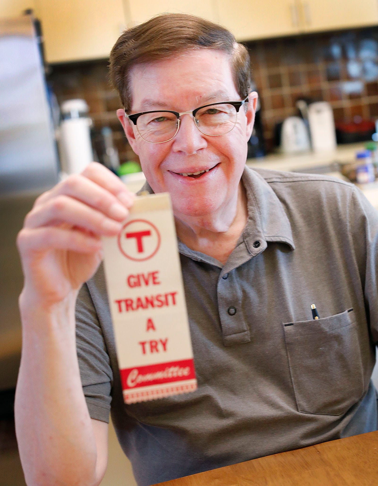 Bradley Clarke, of Boston, a transit historian and president of The Boston Street Railway Association, holds memorabilia from the opening of the Red Line extension in Quincy on Thursday, July 29, 2021.