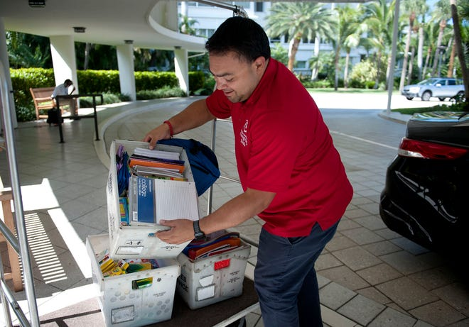 Gaby Alvarez, activities manager for American Association of Caregiving Youth, picks up school supplies collected by Town of Palm Beach United Way on July 29.