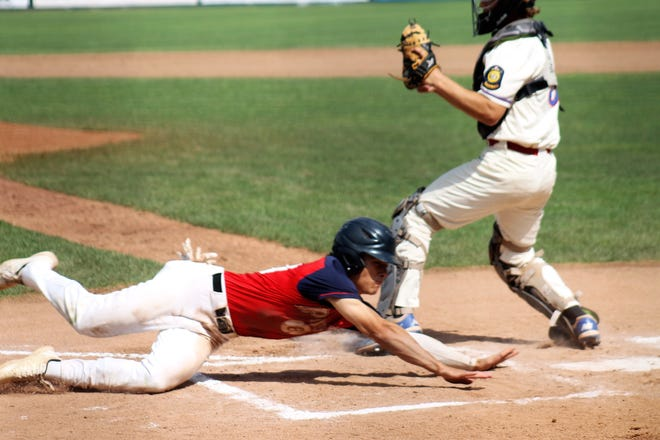 Portsmouth's Will Hindle slides head first across home plate as part of a double steal that gave Booma Post a 2-0 lead in the first inning of Wednesday's championship against Nashua at Holman Stadium.