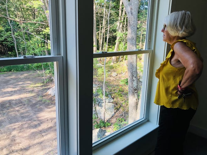 Susan Mosher takes in the backyard view at the brand new home at Heritage Woods. On Wednesday, the Kennebunkport Heritage Housing Trust provided tours of the residence, its first to be completed in its goal of building 25 affordable homes in the community by 2025.
