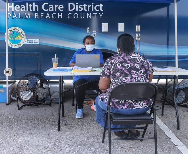 Health Care district employee Lekeatha Harris registers a woman for a Covid-19 vaccination outside the Palm Beach County Public Health Department in Lantana, FL, July 28, 2021.