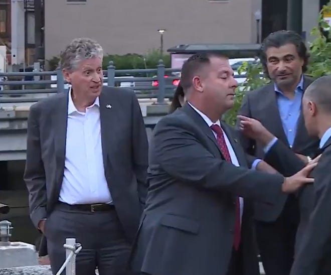 Mayor Jorge Elorza is restrained by a state police officer as he points at Gov. Dan McKee.