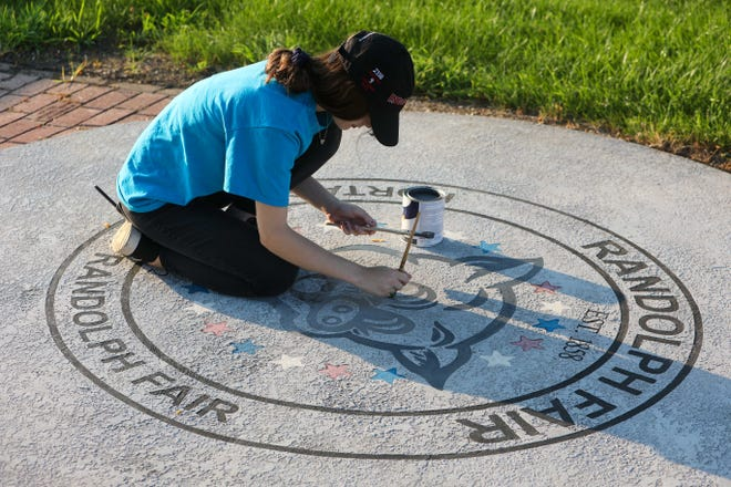 Portage County Randolph Junior Fair Board member Tess Galloway repaints the fair logo in front of the gazebo at the fairgrounds. This year's fair starts on Tuesday.
