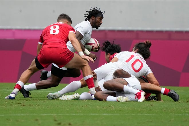 Carlin Isles of the United States, center, gets past Canada's Justin Douglas, left, on his way to score a try in their men's rugby sevens 5-8 placing match at the 2020 Summer Olympics, Wednesday, July 28, 2021 in Tokyo, Japan. (AP Photo/Shuji Kajiyama)