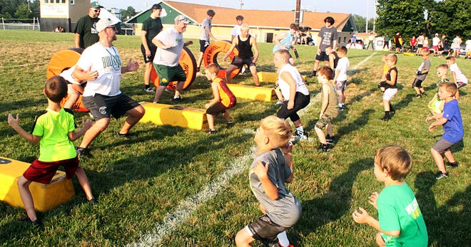 Young Monrovia campers try to emulate what the coaches, including Andy Olson (left), are teaching them about proper tackling stances.