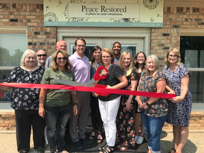 Representatives from Peace Restored and the Mooresville Chamber of Commerce cut the ribbon on the organization's new office located at 460 Saint Clair Street.
