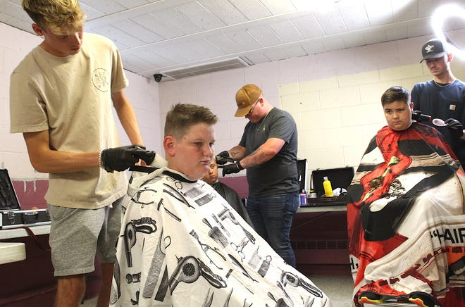 Chase Gilliland gets a haircut from Devin Blackwell at the Momentum Community Church Wednesday afternoon. Free haircuts were offered at the church. Free haircuts will also be available Saturday at the Bedford First Church of God from 9 am until noon. The free haircut effort , which is in its second year, is put together by Heidi and Gage Forrest. In the background are, (center), Carsen Wheelock, getting his hair cut by Parish England, employed by the Fire House Barbershop in Bedford, and Desco Hinojosa, getting his hair cut by Gage Forrest, who is employed by The Back Porch Barbershop in Mitchell.