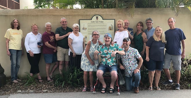 On May 22, the Spanish Quarter Neighborhood Association held its yearly meeting. At the conclusion of the meeting, members met in front of the Little San Felipe sign. The sign describes the lives of the Menorcans who lived in this area in the 1700s and where today some of the Menorcan families still live. From left, Carol Seddon, Vickie Bliss, Rhonda Carter, Leonard Pellicer, Nancy Pellicer, Theresa Traywick, Emery McClune(seated), Brian Funk, Martha Mickler, Ron Mickler, Michaele O'Neil, Julio Torres, Jane Williams and James Willliams.