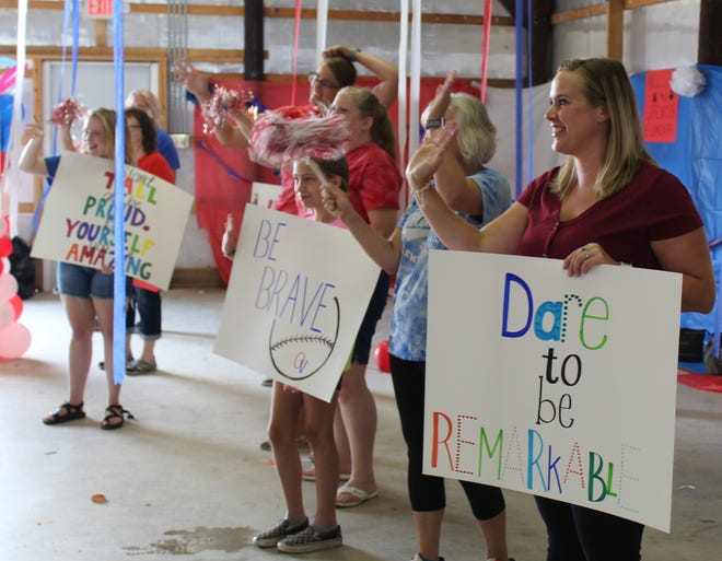 Faculty and staff wave to school children and families during the backward parade.