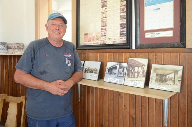 Ed Malle, owner of Malle Service & Tire, shown here with photos of the shop from its earliest days, announced this week that the business will be closing permanently.
