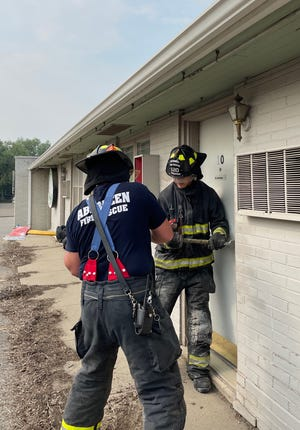 Firefighters Carter Deyo, left, and Hunter Schlotman, use an ax and a halligan to pop open a door. Aberdeen Fire & Rescue was practicing a variety of methods used to fight fires  on the building, which will soon be demolished.