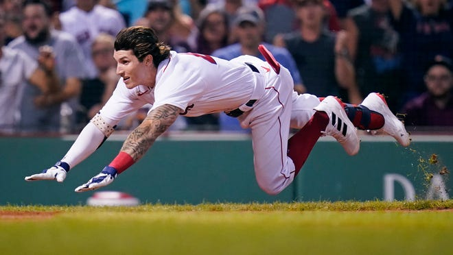 Boston Red Sox's Jarren Duran dives home to score against the Toronto Blue Jays during the Red Sox's 4-1 win  at Fenway Park.